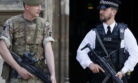 An armed soldier and policeman stand guard at Parliament, in London, Thursday, May 25, 2017.