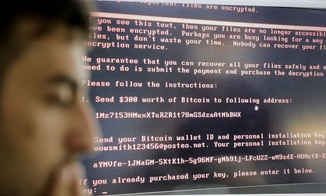 Razvan Muresan, a Bitdefender public relations specialist is backdropped by a screenshot of the message displayed on computers affected by the latest cyberattack, in Bucharest, Romania, Wednesday, June 28, 2017.