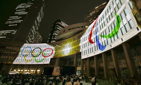 Olympic logos are projected on Tokyo Metropolitan Government building during the Tokyo 2020 flag tour festival for the 2020 Games in Tokyo, Monday, July 24, 2017.