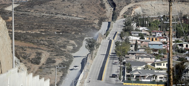 A Border Patrol vehicle drives by the border fence in Tecate, Calif., left, along the metal barrier that lines the border Wednesday, Nov. 9, 2016, seen from Tecate, Mexico.