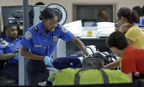 A Transportation Security Administration officer checks travelers luggage to be screened by an x-ray machine at a checkpoint at Fort Lauderdale-Hollywood International Airport, Friday, May 27, 2016.