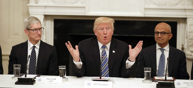 President Donald Trump, center, speaks as he is seated between Tim Cook, Chief Executive Officer of Apple, left, and Satya Nadella, Chief Executive Officer of Microsoft, right, during an American Technology Council roundtable at the White House.