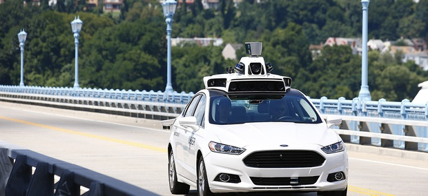 Uber employees test a self-driving Ford Fusion hybrid car, in Pittsburgh.