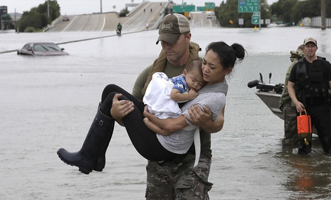 Houston Police SWAT officer Daryl Hudeck carries Catherine Pham and her 13-month-old son Aiden after rescuing them from their home surrounded by floodwaters from Tropical Storm Harvey Sunday, Aug. 27, 2017.