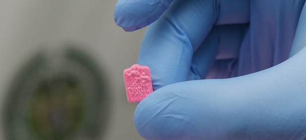 A police officer holds a single MDMA tablet, also known as ecstasy.