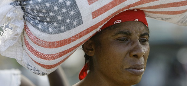 a woman carries a bag containing rice donated by the United States Agency for International Development.