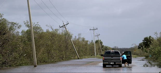 A motorist stands in water on a flooded road from Hurricane Irma leading to Marco Island, Fla., Monday, Sept. 11, 2017.