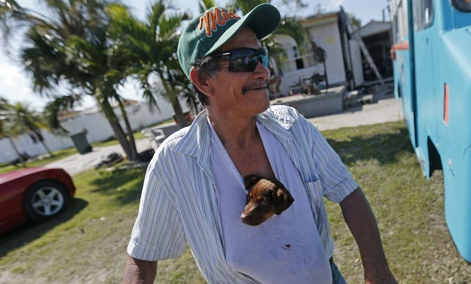 "Nicolas Perez keeps a puppy he named ""Irma,"" stuffed in his shirt, who he rescued from flooding in the aftermath of Hurricane Irma, in Immokalee, Fla."
