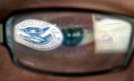 A reflection of the Department of Homeland Security logo is seen reflected in the glasses of a cyber security analyst in the watch and warning center at the DHS's secretive cyber defense facility at Idaho National Laboratory.