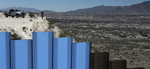 An agent of the border patrol, observes near the Mexico-US border fence, on the Mexican side.