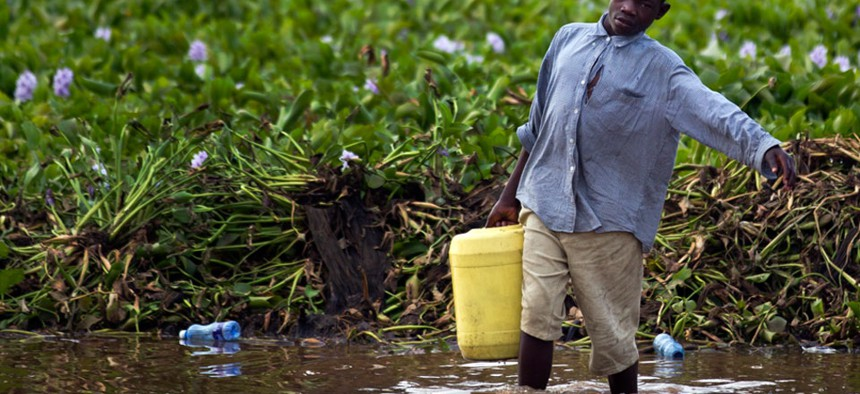 A man gathers water from Lake Victoria in Kisumu, Kenya.