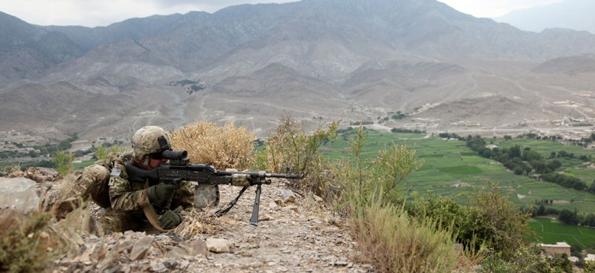 A soldier provides security from a hilltop during a patrol in Paktia province in August.