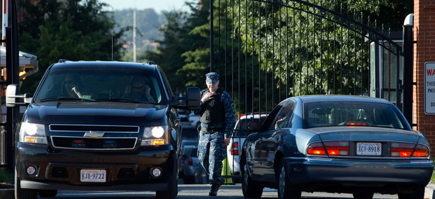 A member of the Navy checks vehicles at a gate to the Washington Navy Yard.