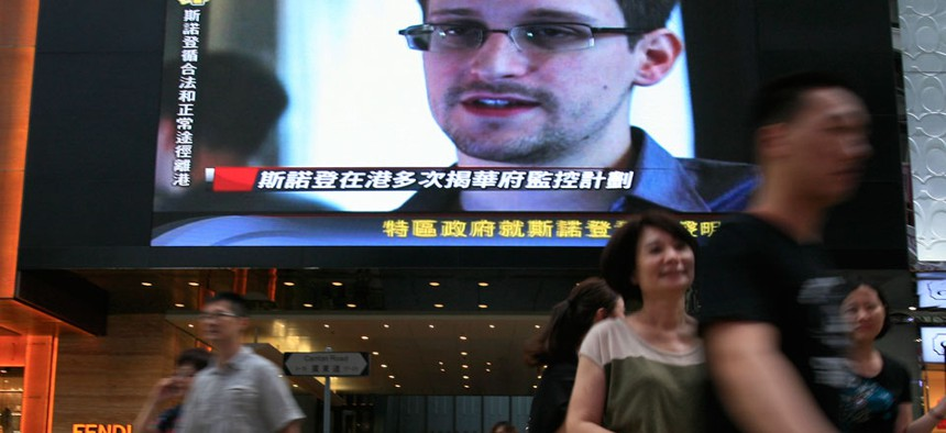 A TV screen shows a news report of Edward Snowden in Hong Kong in June.