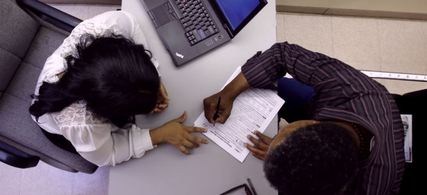 Clinical applications counselor Rachael Richardson, left, works with Louis Peters at the Henry J. Austin Health Center, in Trenton, N.J., as he and others fill out papers to sign up for new plans through the health insurance exchange.