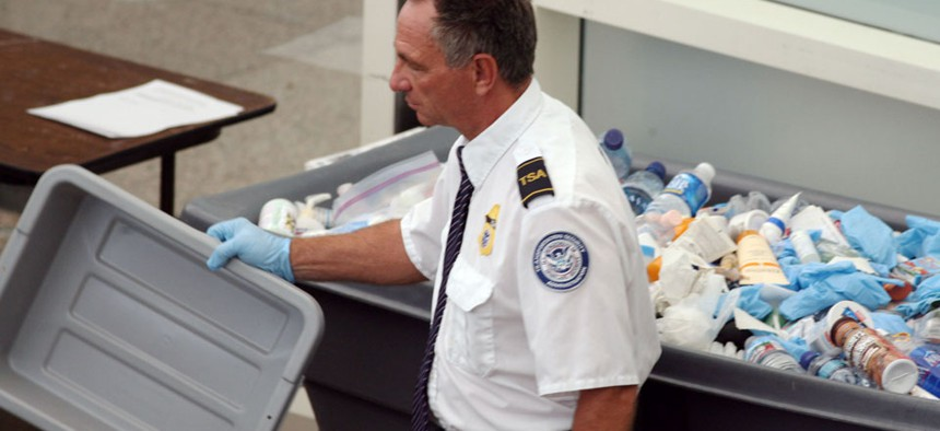 A  TSA worker empties bottles into a bin filled with confiscated items at Denver International Airport.