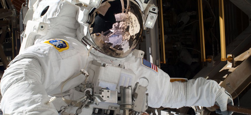 NASA astronaut Michael Hopkins, Hopkins work to repair an external cooling line on the International Space Station 260 miles above the Earth.