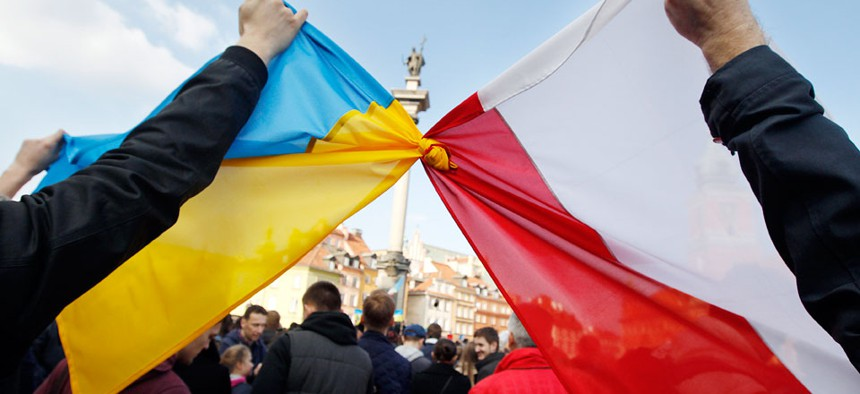 People hold tied Polish, right, and Ukrainian flags during a demonstration supporting the opposition movement in Ukraine, in Warsaw, Poland.