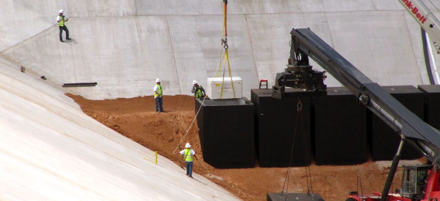Commercial crews load the first of two containers with low-level radioactive waste from Los Alamos National Laboratory.