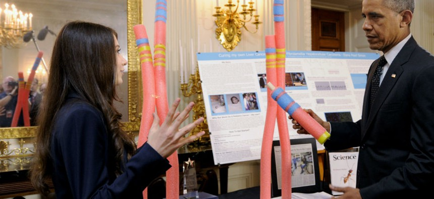 President Barack Obama talks with Elana Simon, 18, of New York City, about her cancer research project that is part of the 2014 White House Science Fair exhibit.