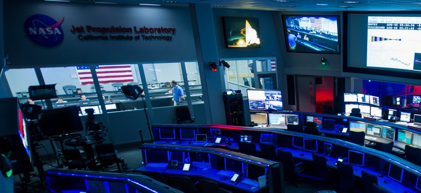 The the control rooms at the Jet Propulsion Laboratory, the Dark Room in the foreground, Deep Space Network control room on the right and the Mars Science Laboratory Mission Support Area back left.