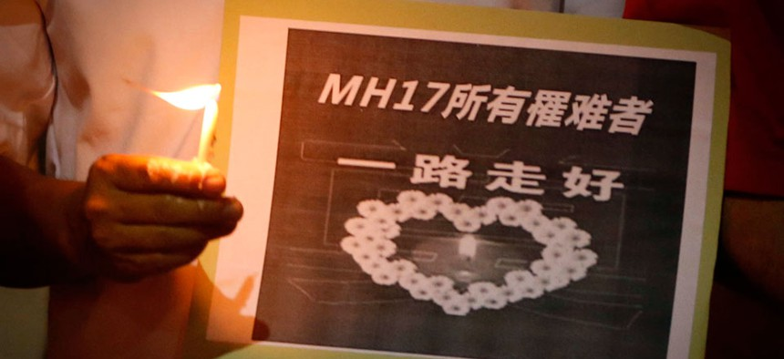 """A man holds a sign which reads """" MH17 Victims Rest In Peace"""" during a candlelight vigil for the victims who were on board the Malaysia Airlines jetliner."""