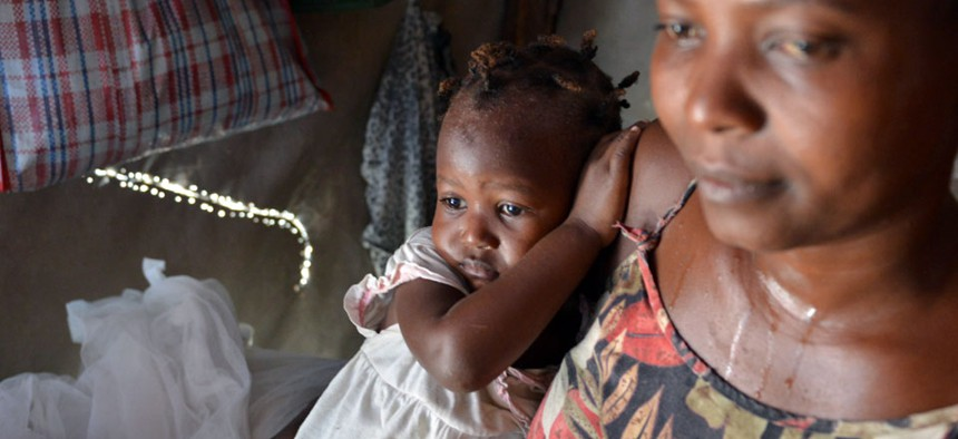 Delimene Saint Lise holds her 2-month-old daughter Gisline inside their tent home in the Delmas section of Port-au-Prince as the child suffers with Chikungunya, a newly arrived mosquito-borne illness.