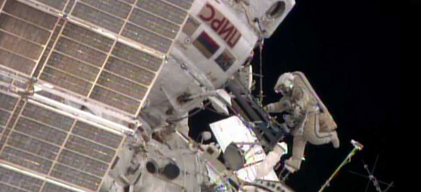While Flight Engineer Alexander Skvortsov retrieves hardware inside the International Space Station's Pirs airlock, Flight Engineer Oleg Artemyev stretches his legs.