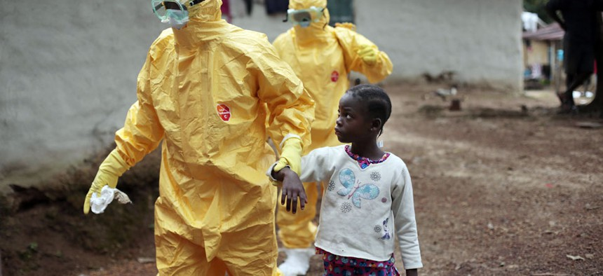 owa Paye, 9, is taken to an ambulance after showing signs of the Ebola infection in the village of Freeman Reserve, about 30 miles north of Monrovia, Liberia.