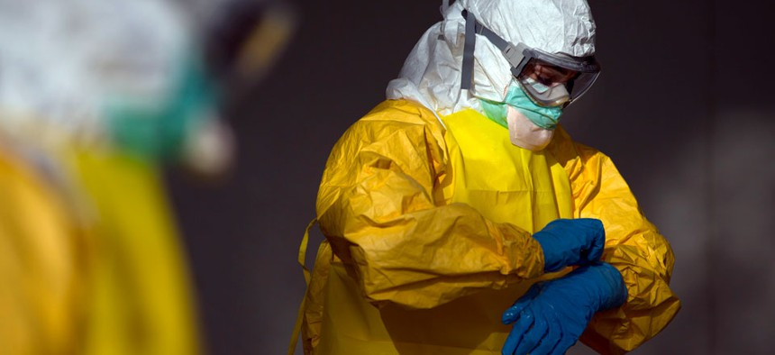 Licensed clinician Margaret Chilcott removes her outer gloves before disrobing and sanitizing during ebola preparation training on Monday, Oct. 6, 2014, in Anniston, Ala.