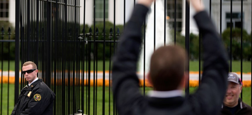 A Secret Service police officer keeps an eye on visitors on the sidewalk in front of the White House in Washington.