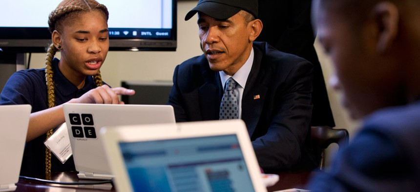 """President Barack Obama is explained a coding learning program by Adrianna Mitchell during an """"Hour of Code"""" event"""