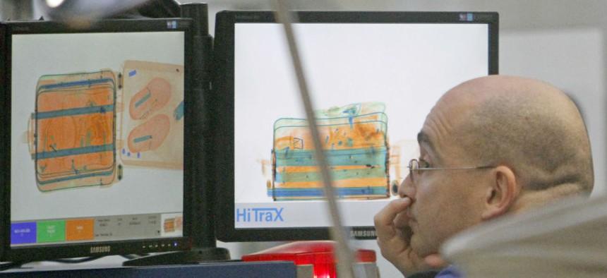A TSA officer checks baggage at Miami International Airport
