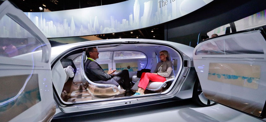Attendees sit in the self-driving Mercedes-Benz F 015 concept car at the Mercedes-Benz booth at the International CES in Las Vegas.