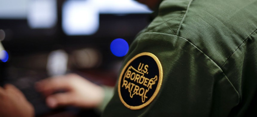 In this June 5, 2014 photo, a Border Patrol agent uses a headset and computer to conduct a long distance interview by video with a person arrested crossing the border in Texas, from a facility in San Diego.