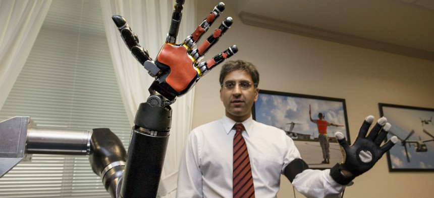 Kapil D. Katyal, an engineer at Johns Hopkins, demonstrates a robotic hand as DARPA displays the latest high-tech projects being developed for wounded soldiers at the Pentagon.