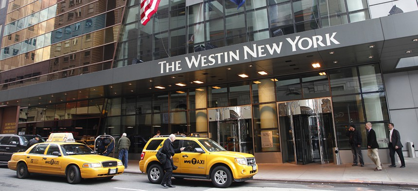A man hails a taxi in front of the Westin New York hotel, a Starwood property.