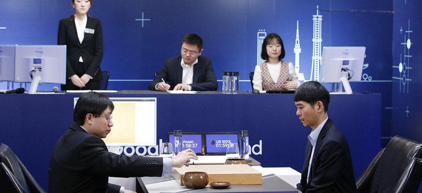 Professional Go player Lee Sedol, right, watches as Google DeepMind's lead programmer Aja Huang, left, puts the Google's artificial intelligence program, AlphaGo's first stone during the final match of the Google DeepMind Challenge Match.