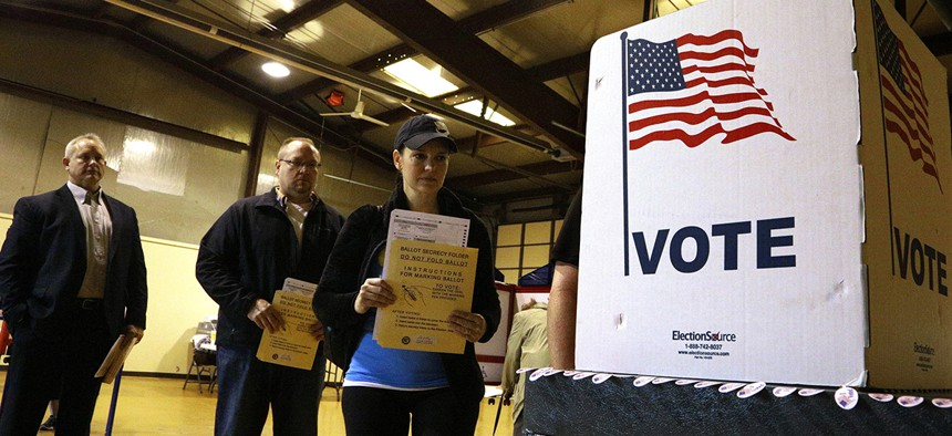 People line up to vote at a precinct Tuesday, March 15, 2016, in Bradfordton, Ill.