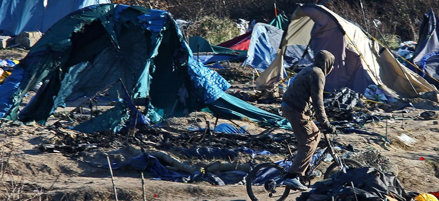 A migrant rides with his bicycle in the Calais refugee camp, northern France Tuesday, Jan. 19, 2016.