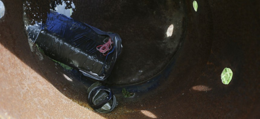 An improvised explosive device sits partially concealed in a barrel during counter-improvised explosive device skills demonstration training exercise at Camp Lejeune, N.C., Sept. 1.
