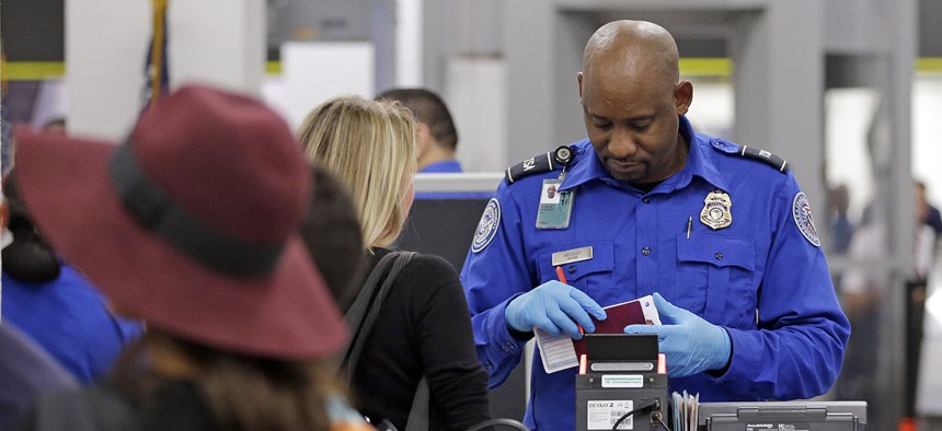 A Transportation Security Administration agent checks traveling documents of a passenger at Miami International Airport.