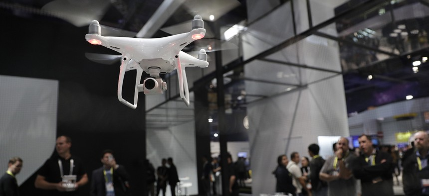People watch a flying demonstration of a drone at the DJI booth at CES International Thursday, Jan. 5, 2017, in Las Vegas.