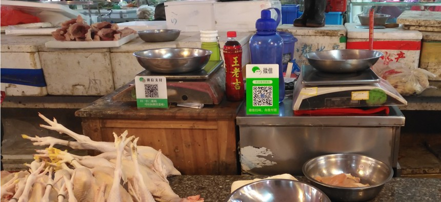 Retailers in a Chinese market use WeChat QR code payment symbols to collect payments.