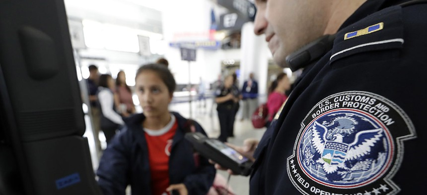 U.S. Customs and Border Protection officer Julio Corro, right, helps a passenger navigate one of the new facial recognition kiosks at a United Airlines gate before boarding a flight to Tokyo, Wednesday, July 12, 2017.
