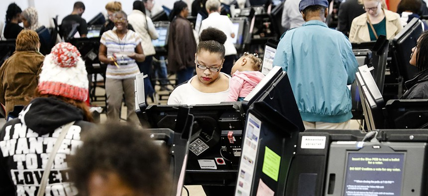 Early voters use electronic ballot casting machines at the Franklin County Board of Elections, Monday, Nov. 7, 2016, in Columbus, Ohio.