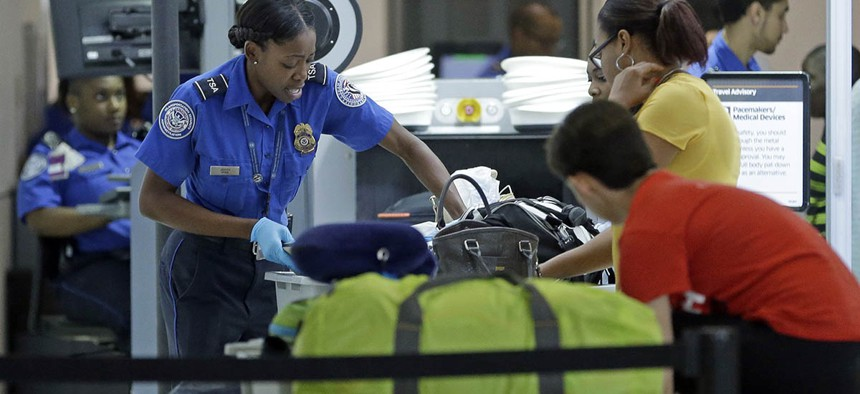 A Transportation Security Administration officer checks travelers luggage to be screened by an x-ray machine at a checkpoint at Fort Lauderdale-Hollywood International Airport.