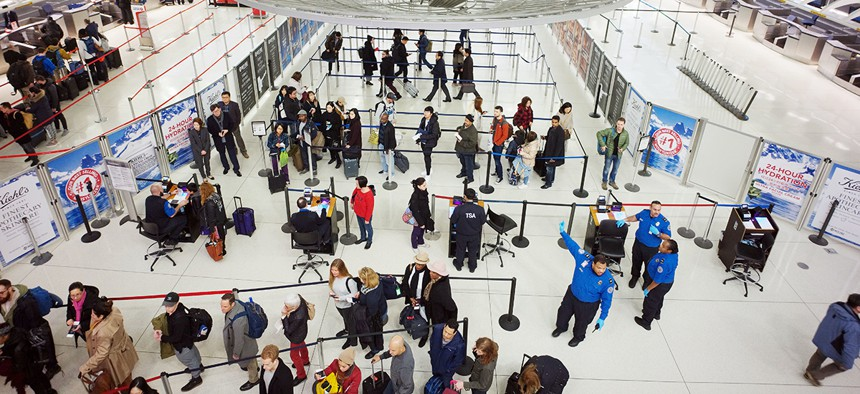 passengers stand in line as they wait to pass through a TSA security checkpoint at JFK International Airport.
