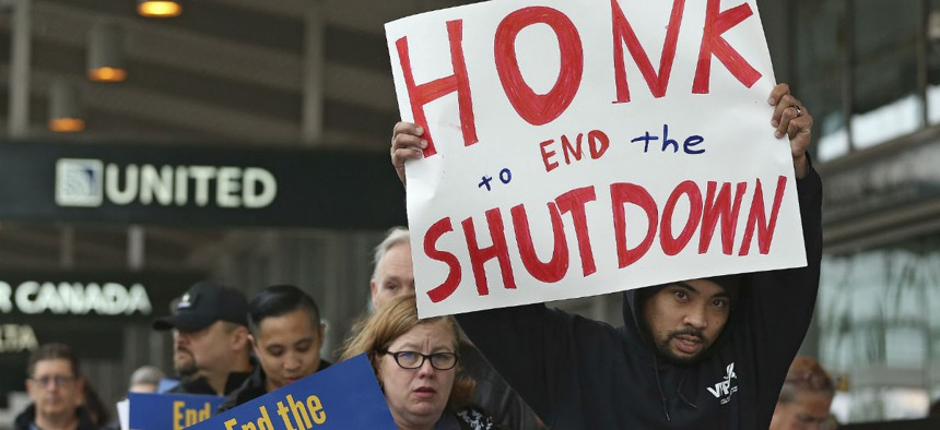 More than two dozen federal employees and supporters demonstrate at the Sacramento International Airport calling for lawmakers to end the partial government shutdown.