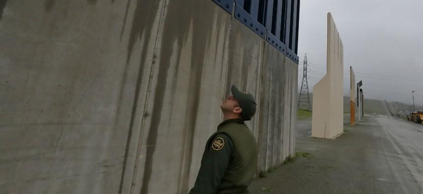 A Border Patrol agent walks towards prototypes for a border wall Feb. 5 in San Diego.